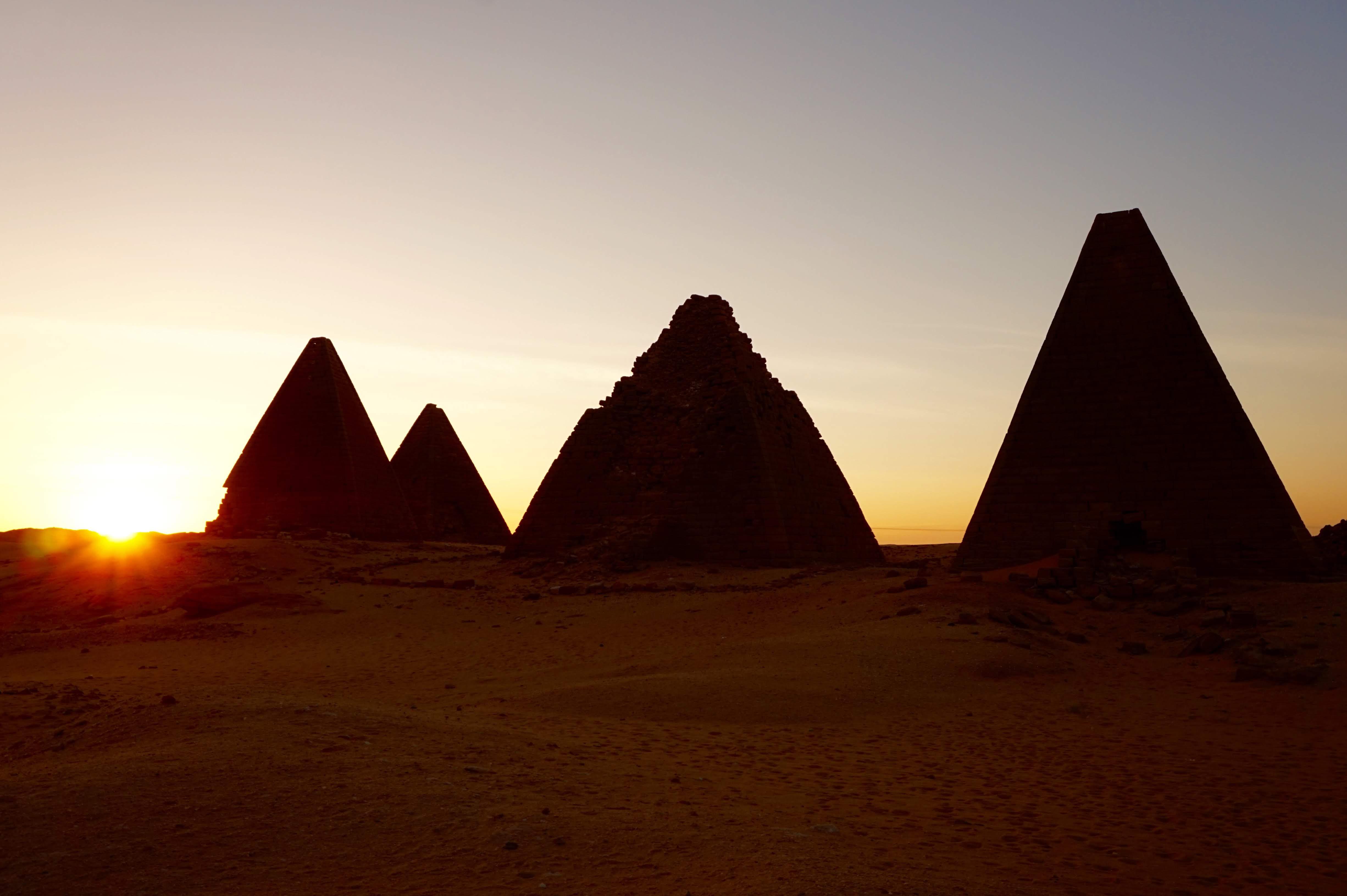 TheSunSetsBehindThePyramidsAtTheBaseOfJebelBarkalMountain