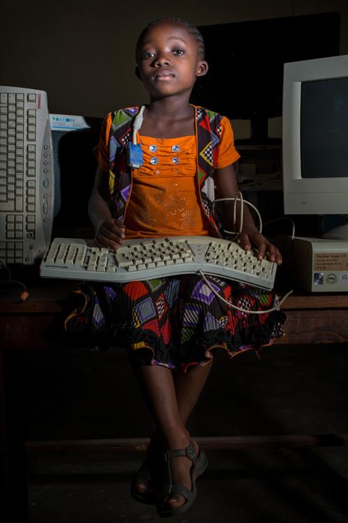 """Sifa est une fille de 8 ans habitant Kapolo, un quartier pauvre de Kalémie, la capitale de la province du Tanganyika, une région en proie depuis un an à des violences inter-ethniques qui ont provoqué le déplacement de plus de 500.000 personnes. Bien qu'habitant un quartier défavorisé, son père possède un ordinateur portable. Comme lui, elle souhaite manipuler des ordinateurs. Elle rêve de «devenir technicienne informatique et créer le plus grand centre informatique de Kalémie où les enfants pauvres viendraient apprendre». / Sifa is a 8-year-old girl living in Kapolo, a poor district of Kalémie, the capital of the province of Tanganyika, a region that has been ravaged by inter-ethnic violence for over a year, causing more than 500,000 people to flee. Although living in a disadvantaged neighborhood, his father owns a laptop. Like him, she wants to manipulate computers. She dreams of """"becoming a computer technician and creating the largest computer center in Kalémie where poor children would come to learn""""."""