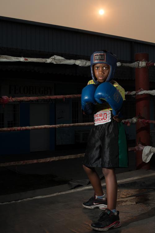 """Josepha, 7 ans, a grandit dans la commune de Kalamu, à Kinshasa, ou se situe le stade du 20 mai, lieu mythique ou s'est déroulé le «combat du siècle» entre Mohamed Ali et Georges Foreman le 30 octobre 1974. Elle rêve de devenir boxeuse comme Mohammed Ali et comme sa cousine, championne de boxe de Kinshasa en catégorie coq, et depuis un an s'entraine dans le club de boxe «La tête haute de Mohammed Ali», où elle la seule petite fille, sans complexe, au milieu d'une dizaine de petits garçons, boxeurs en herbe. / Josepha, 7, grew up in the Kalamu commune in Kinshasa, where the May 20th stadium is situated, a mythical place where took place the """" Rumble in the Jungle """" between Mohamed Ali and Georges Foreman on October 30th, 1974. She dreams of becoming a boxer like Mohammed Ali and like her cousin, boxing champion of Kinshasa in cock category, and since a year trains in the boxing club """"La tête haute de Mohammed Ali"""", where she is the only girl, fearless, amidst a dozen little boys, budding boxers."""