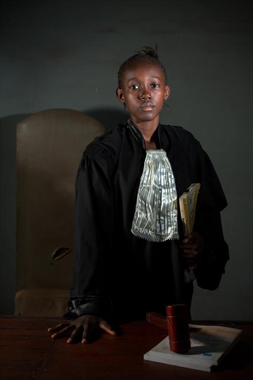 """Depuis qu'elle a 4 ans, Ruth, qui est maintenant âgée de 12 ans, combat les injustices et défend les enfants punis à tord par les adultes, ce qui lui a valu le surnom «d'avocate» auprès de ses parents. En 2013, le visionnage d'un film parlant du combat d'un avocat pour faire libérer un innocent confirme sa vocation précoce. En tant que scout de la Croix-Rouge de Mbandaka, Ruth a appris quelques notions de droit humanitaire. Un fois ses études secondaires terminées, elle souhaite étudier le droit pour devenir avocate. / Since she was 4 years old, Ruth, now 12 years old, is fighting injustices and defending children who have been wrongly punished by adults, which earned her the nickname """"lawyer"""" with her parents. In 2013, watching a film about a lawyer's struggle for the release of an innocent man confirms his precocious vocation. As a Scout of the Mbandaka Red Cross, Ruth learned a few notions of humanitarian law. After completing high school, she wants to study law to become a lawyer."""