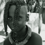 Kaokoland is home to the Himba. Little girls wear - before reaching puberty - two braids hanging into the face. When they pass puberty, their hair is woven into a couple of smaller braids decorated with leather and pearls