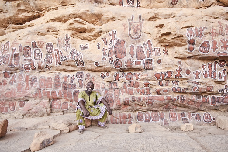 Dolo, one of the elders of Songho sits in front of the murals that serve as intermediaries between men and the gods.